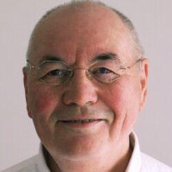 Paul van der Vliet man grey hair older glasses smiling